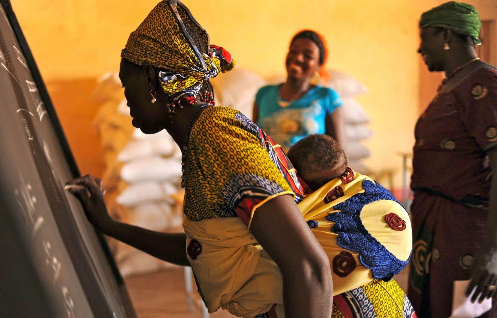 Kalizeta lors d'un cours d'alphabétisation en dioula au centre d'étuvage de l'Union des groupements d'étuveuses de riz de Bama, au Burkina Faso