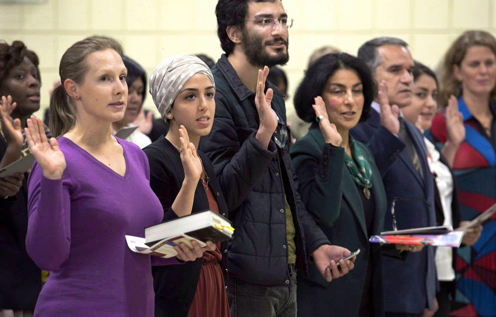 Des immigrants ayant obtenu la citoyenneté canadienne prêtent serment à l'occasion d'une cérémonie.