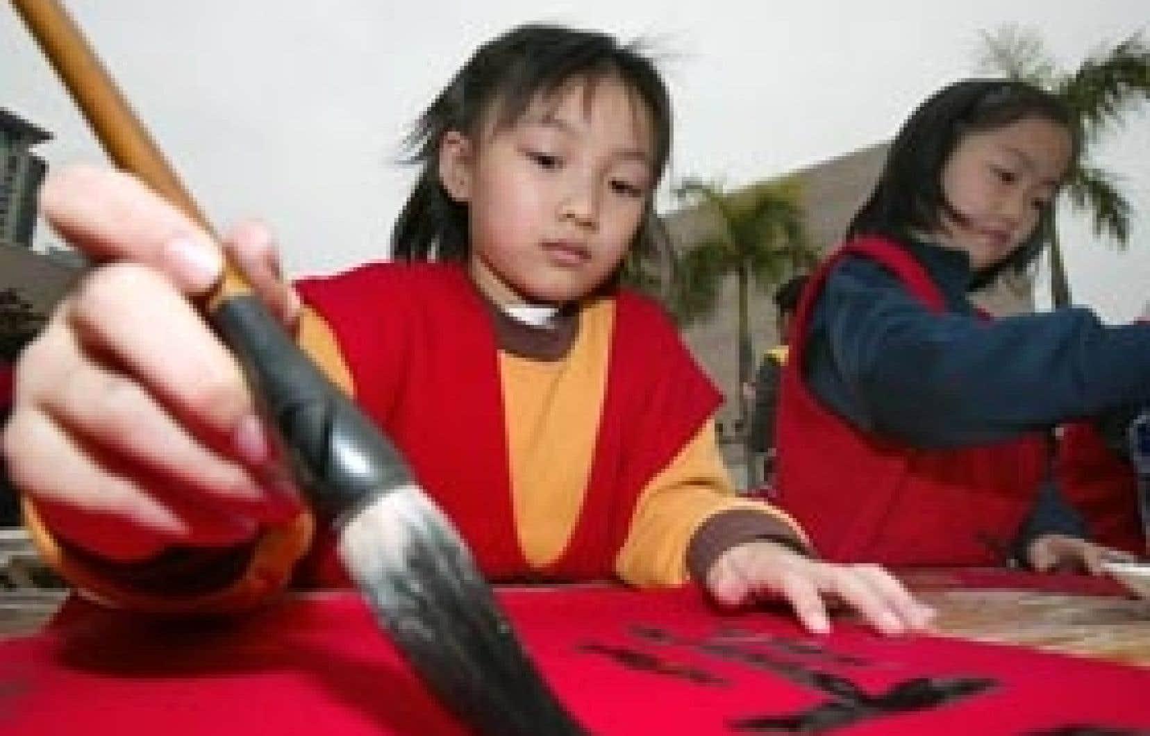 Des fillettes s'adonnant à la calligraphie à Hong Kong. La logique de la langue chinoise a inspiré à des chercheurs québécois le projet de créer un langage animé universel.