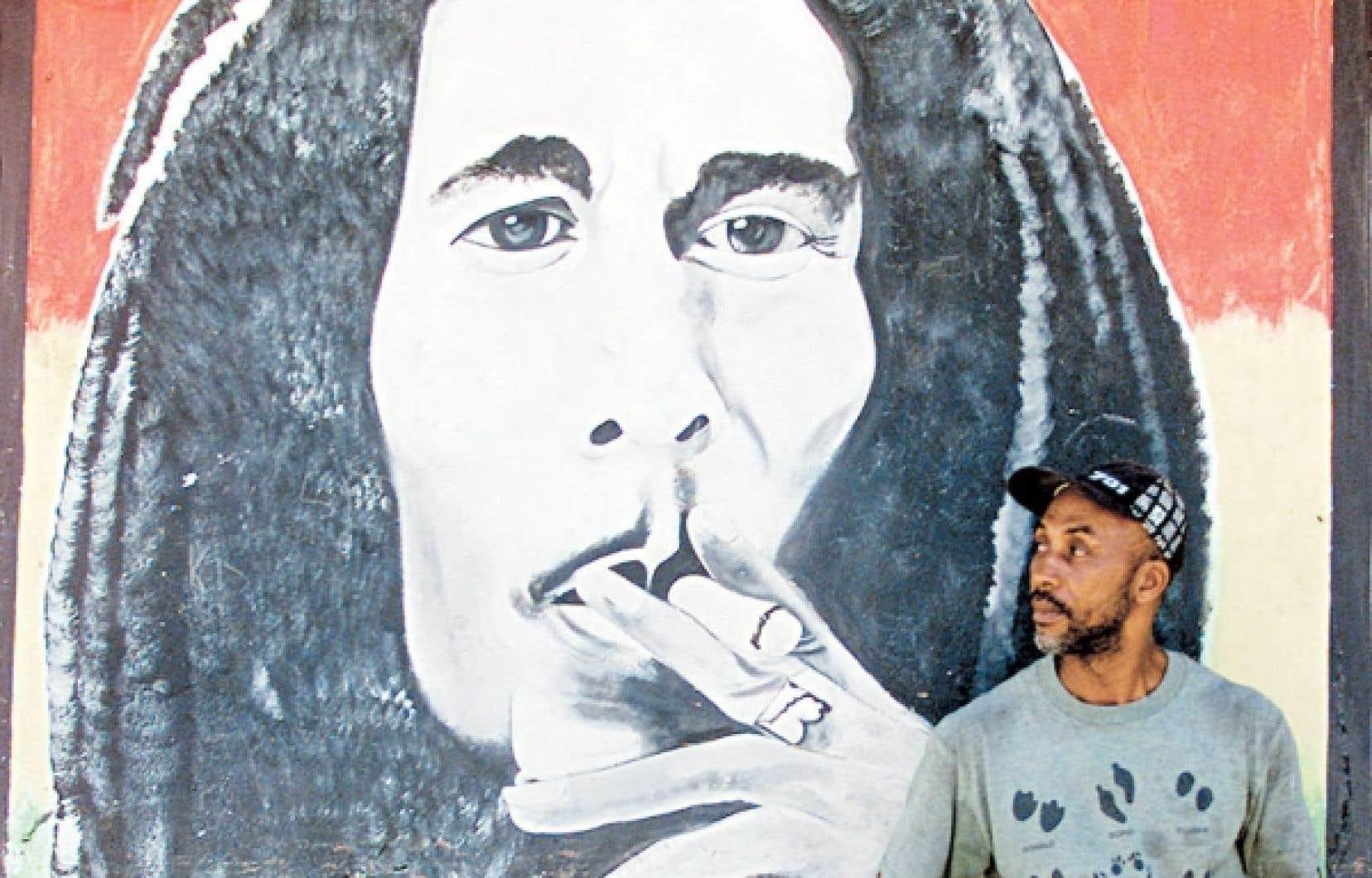 Un passant devant une murale figurant Bob Marley, à Kingston en Jamaique