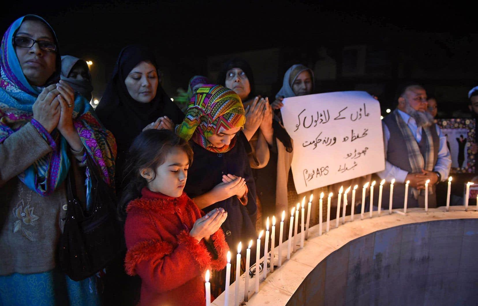 Au moins 21 personnes ont été tuées mercredi dans l'attaque d'une université du nord-ouest du Pakistan revendiquée par une faction talibane, provoquant l'émoi dans le pays un an après un massacre dans une école de la même région. En photo, des proches des victimes de l'attentat de l'école militaire de Peshawar de décembre 2014 — 141 personnes avaient été tuées — se recueillent en mémoire des étudiants universitaires.