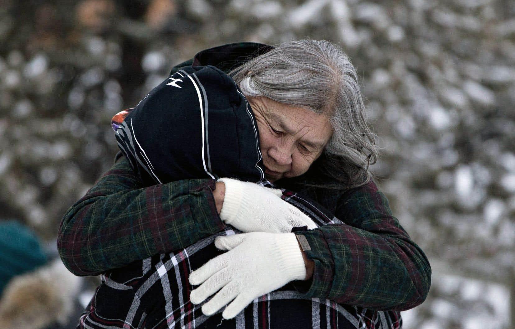 Des membres de la communauté à majorité autochtone se réconfortaient, dimanche, près d'un mémorial en l'honneur des victimes.