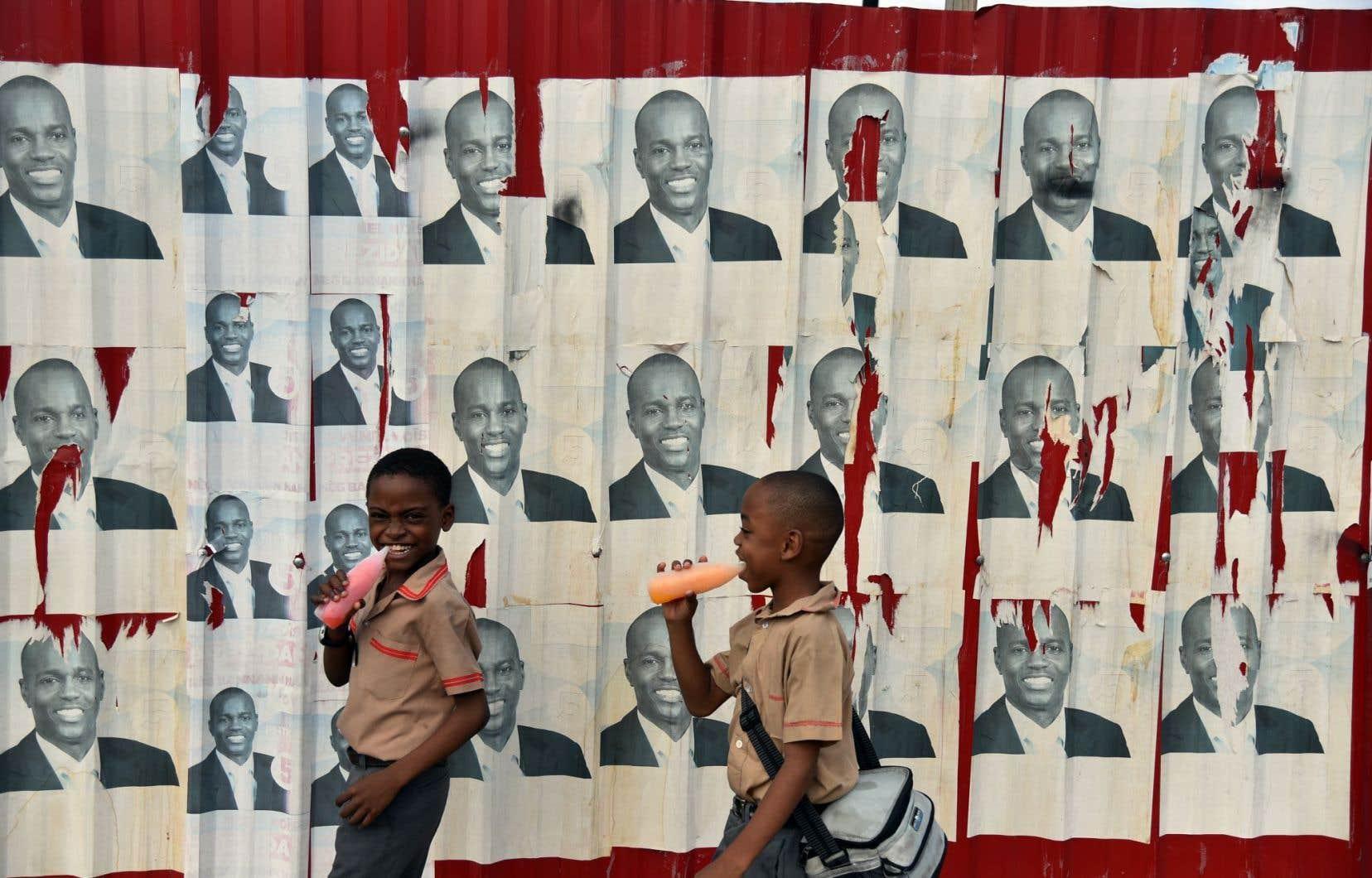 Des écoliers de Port-au-Prince passent devant les affiches du candidat à la présidence du Parti haïtien Tèt Kale (PHTK), Jovenel Moïse.