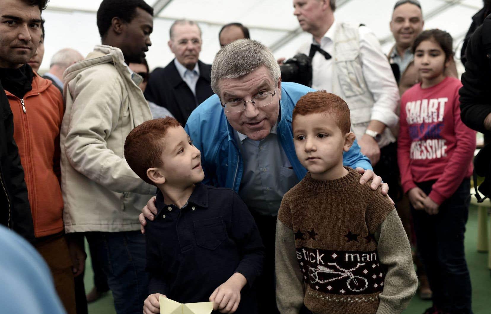 Le président du CIO, Thomas Bach, photographié avec de jeunes réfugiés à l'occasion d'une visite dans un camp à Athènes