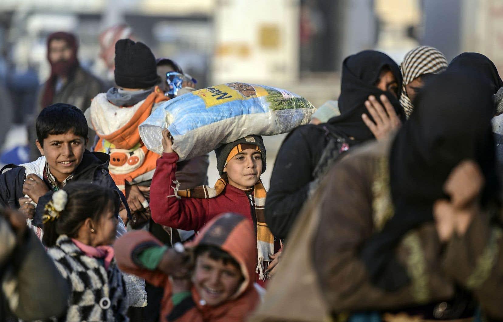 Des Syriens qui ont fui les combats de la province d'Alep se massent au poste-frontière syro-turc de Bab al-Salama.