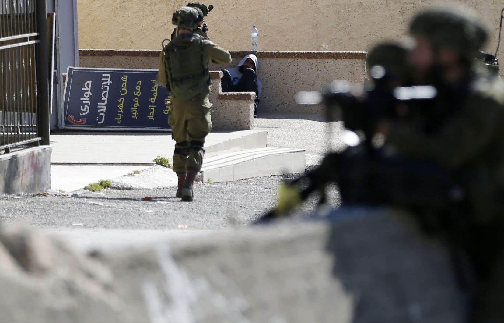 Un soldat israélien tenait en joue un manifestant palestinien lundi dans le camp d'al-Amari.
