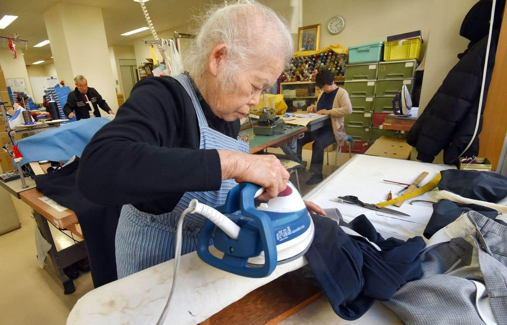 À Tokyo, cette retraitée n'est pas restée longtemps à la maison; la voici dans un atelier de couture, à rapasser des pantalons.