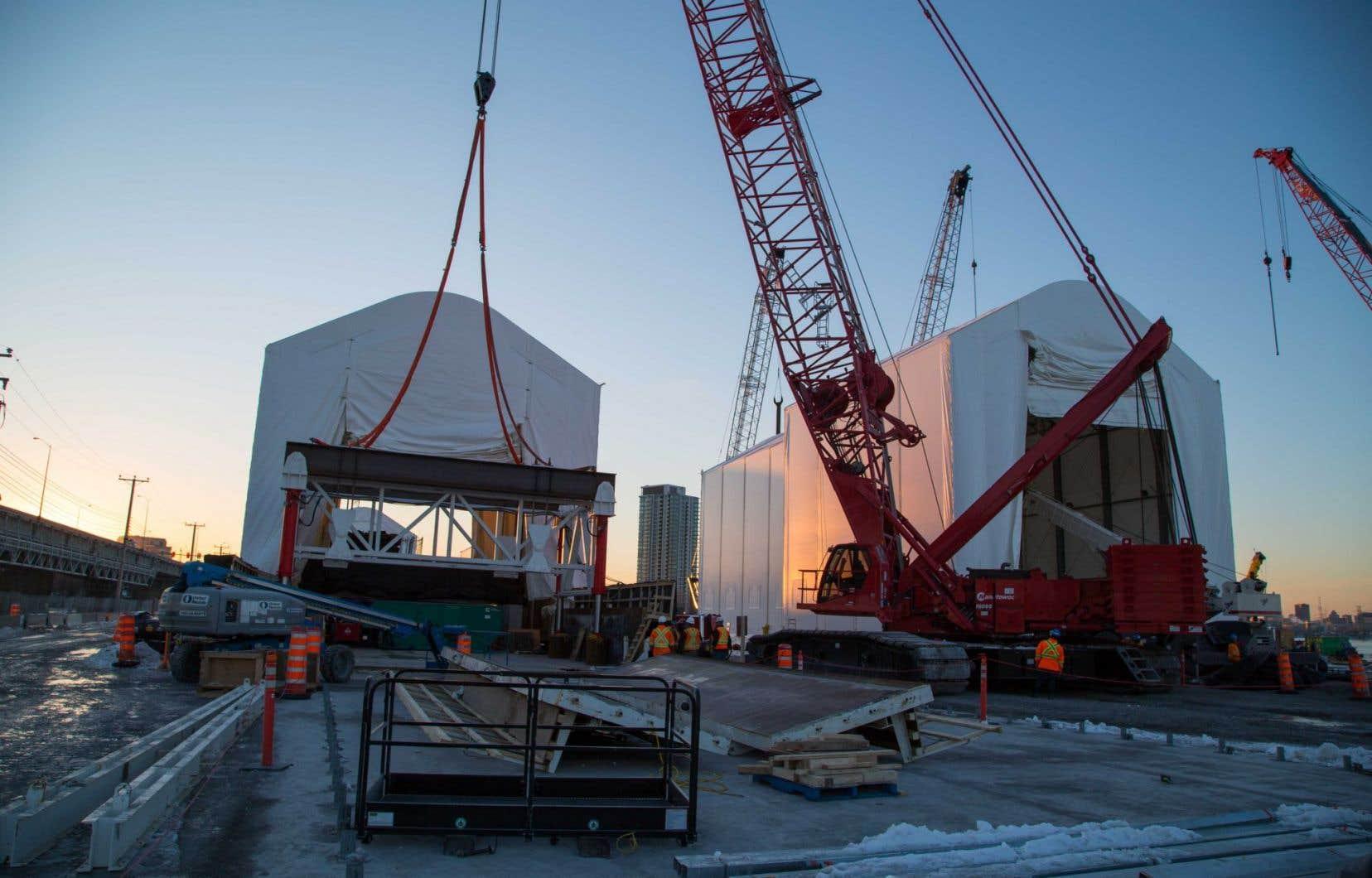 Sous de grandes tentes blanches, une équipe s'affaire à préfabriquer à sec 38 des 74 semelles de béton géantes qui seront bientôt déposées dans le lit du fleuve pour servir d'assises au futur pont.