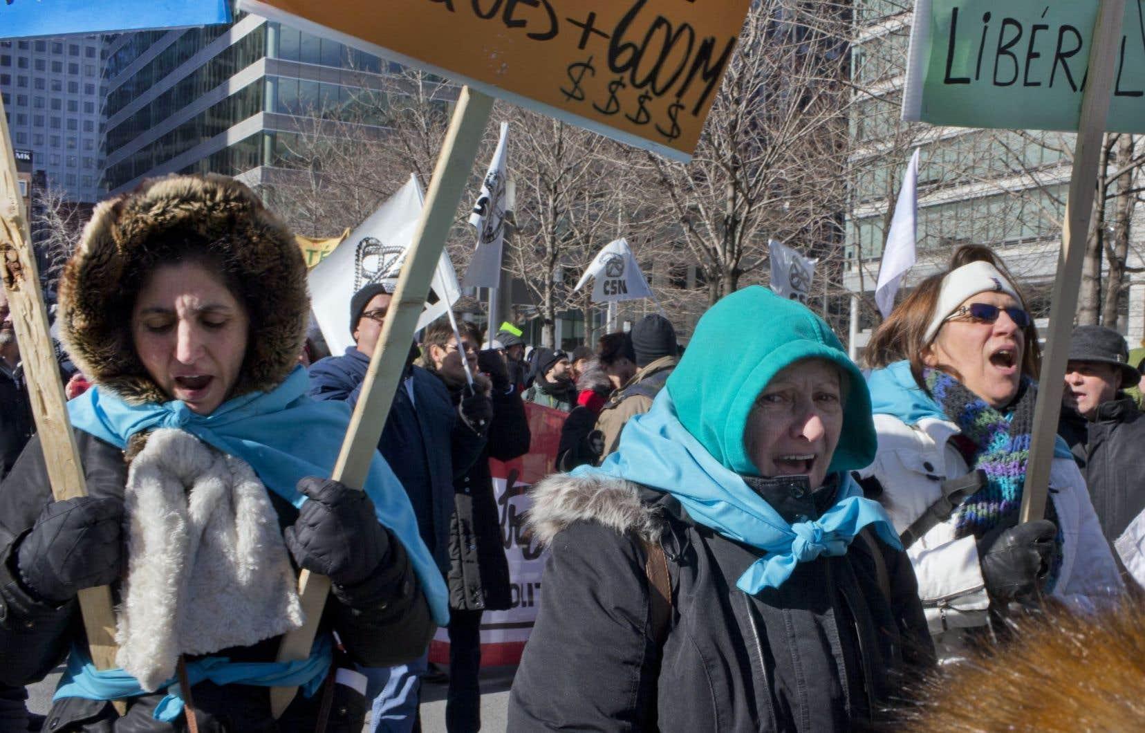 Des femmes manifestent contre les mesures d'austérité du gouvernement Couillard à Montréal, le 23 février.