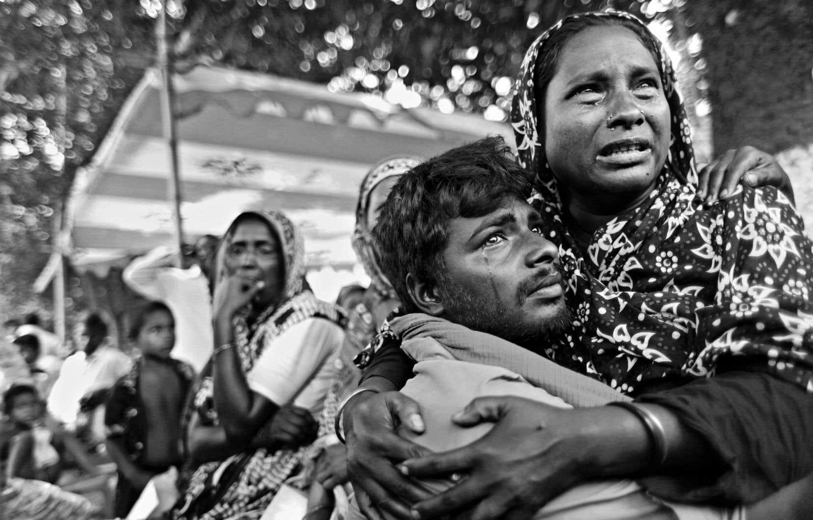 Des parents en deuil alors qu'ils retrouvent le corps de leur fils disparu, 17 jours après l'effondrement du Rana Plaza. Photo tirée de l'exposition «Le goût mortel des vêtements à rabais» d'Abir Abdullah.