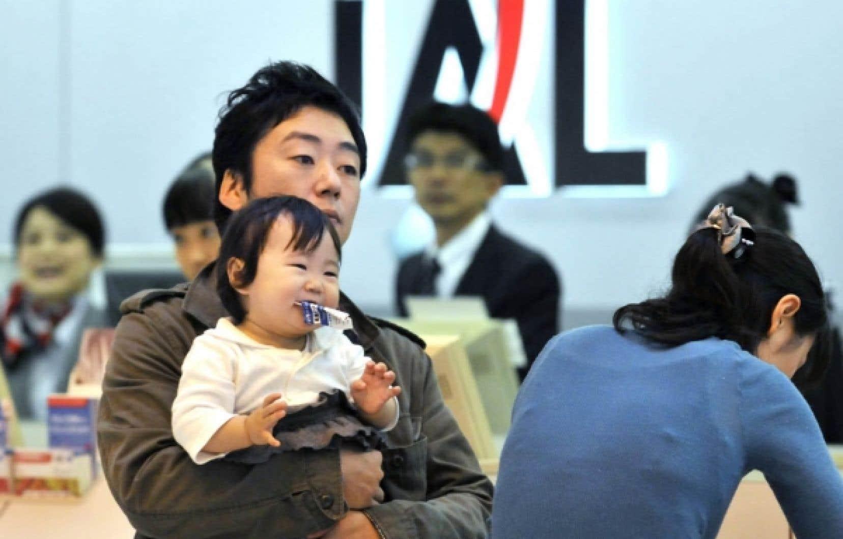 Des passagers attendent leur enregistrement au comptoir de Japan Airlines. Depuis des semaines, American Airlines et Delta Air Lines se disputent âprement les faveurs de JAL, en quasi-faillite et sous tutelle publique, mais qui détient une place stratégique en Asie.