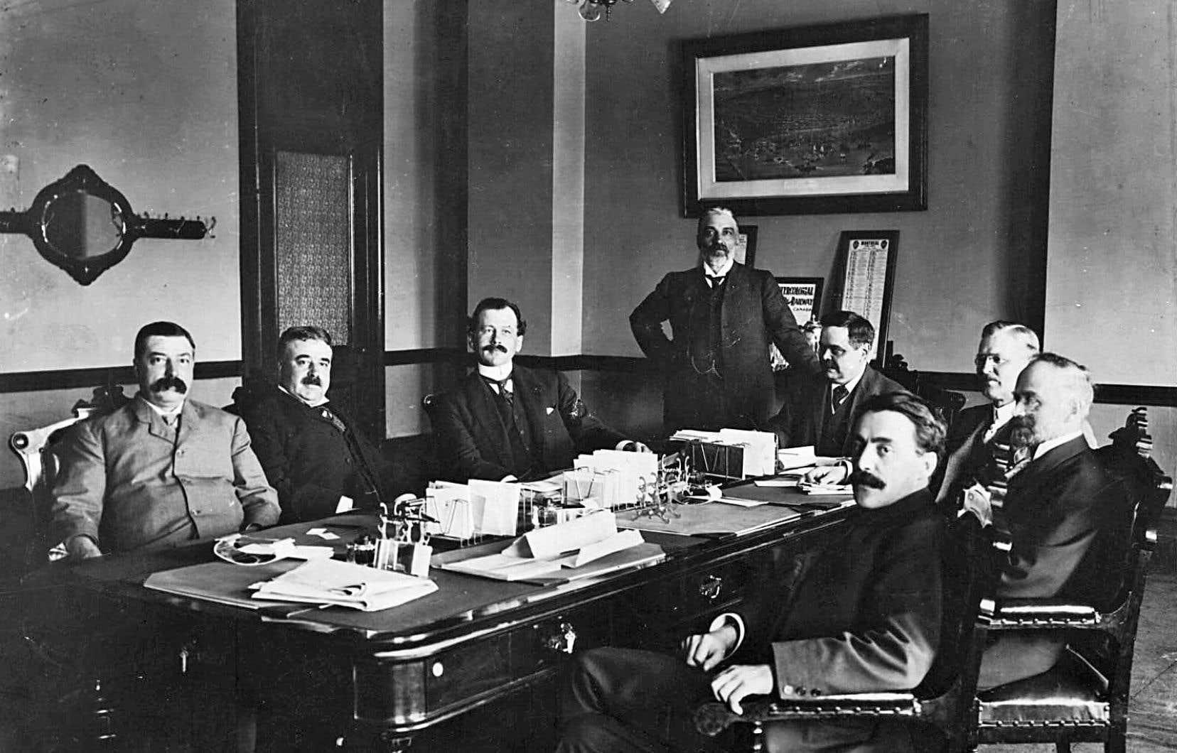 Le premier ministre Lomer Gouin, assis au bout de la table, avec l'ensemble du Conseil des ministres québécois en 1905. À partir de la gauche : Jules Allard, Louis-Rodolphe Roy, Adélard Turgeon, W. A. Weir, Lomer Gouin, J.C. McCorkill, Auguste Tessier et Jean Prévost.