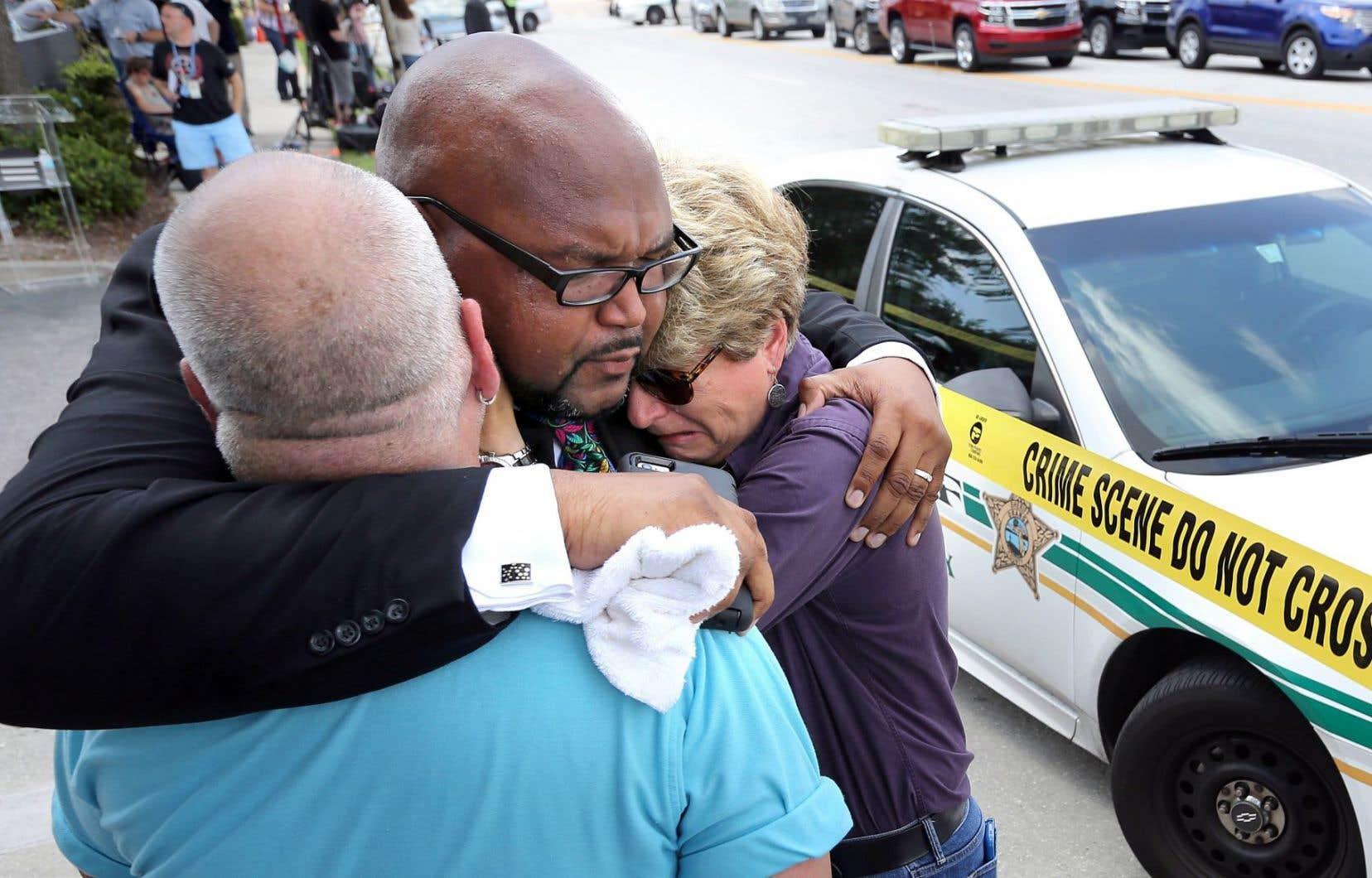 Kelvin Cobaris, un membre du clergé d'Orlando, console la commissaire municipale Patty Sheehan et Terry DeCarlo, un membre de la communauté homosexuelle d'Orlando, près des lieux de l'attentat.