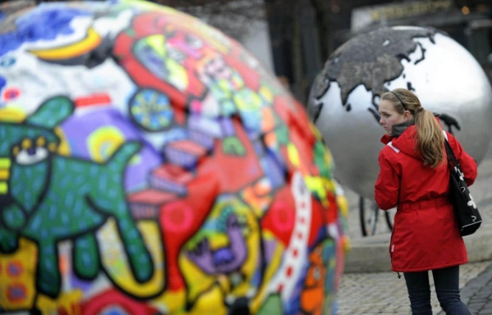 Une passante jette un œil à une exposition installée à Copenhague pour le sommet sur le climat.