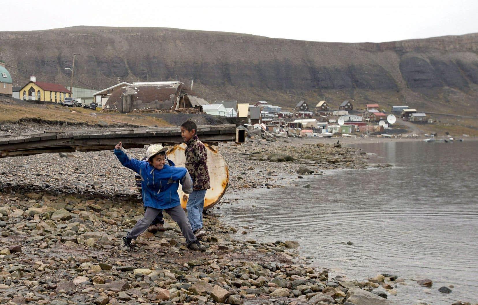 Deux jeunes garçons lancent des cailloux à la mer près d'Arctic Bay, au Nunavut.