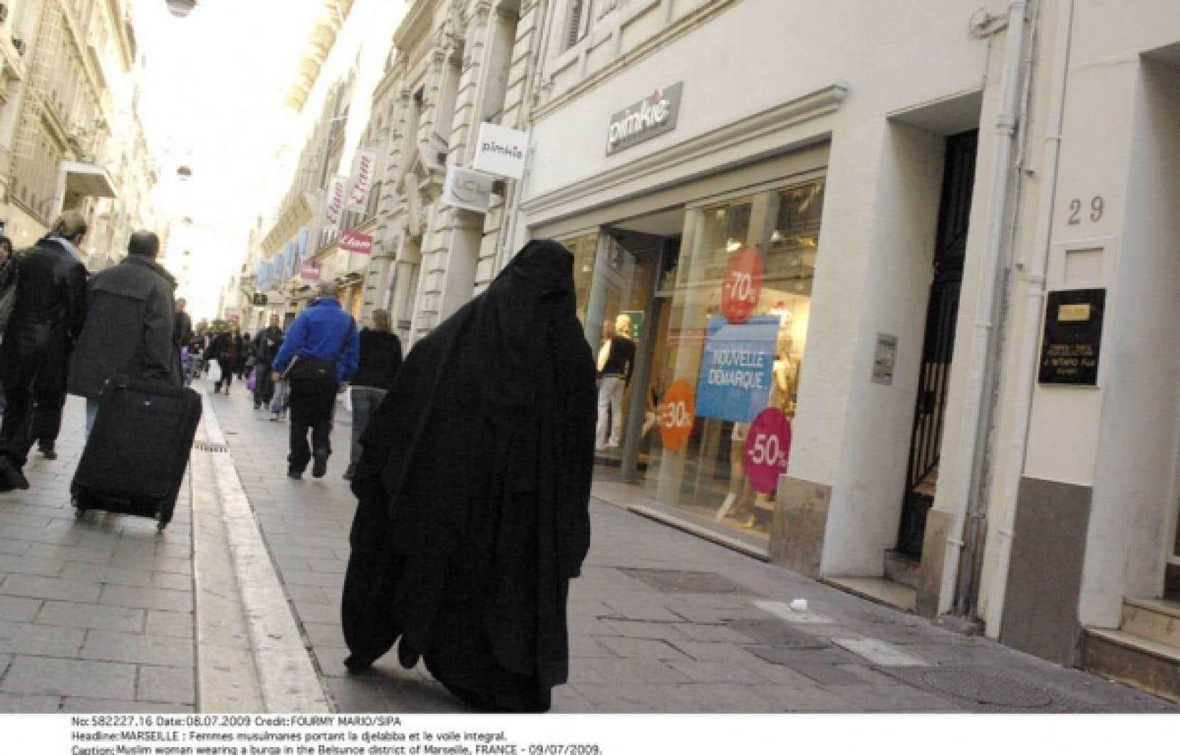 Une femme portant le voile intégral dans une rue de Marseille. À la surprise générale, le dépôt d'un projet de loi visant à interdire la burqa a été annoncé hier.