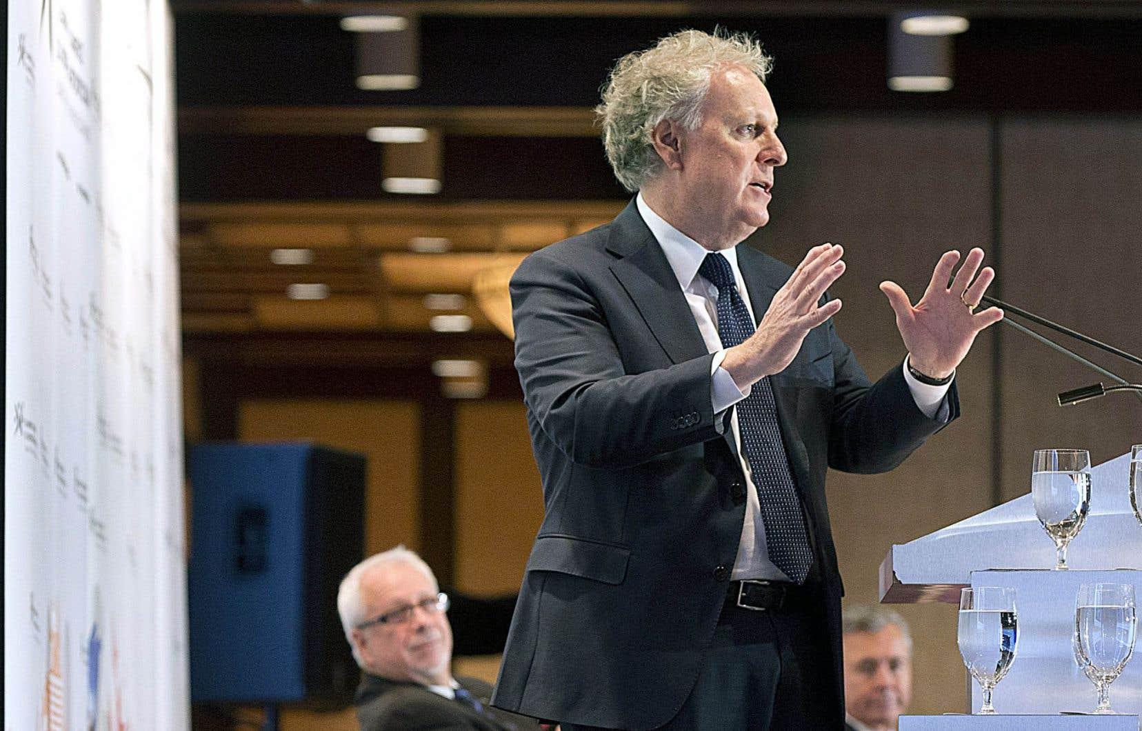 Jean Charest, accompagné sur scène par Pierre Marc Johnson (à gauche), prend la parole lors d'une présentation de l'AECG en octobre 2015.