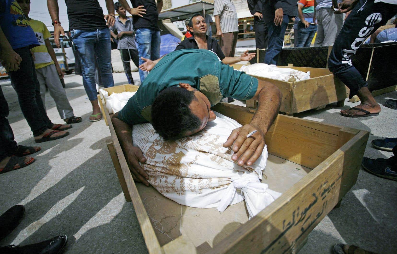 Un homme pleurait sur le corps d'un des membres de sa famille tué à Bagdad lors d'un attentat suicide, dimanche.