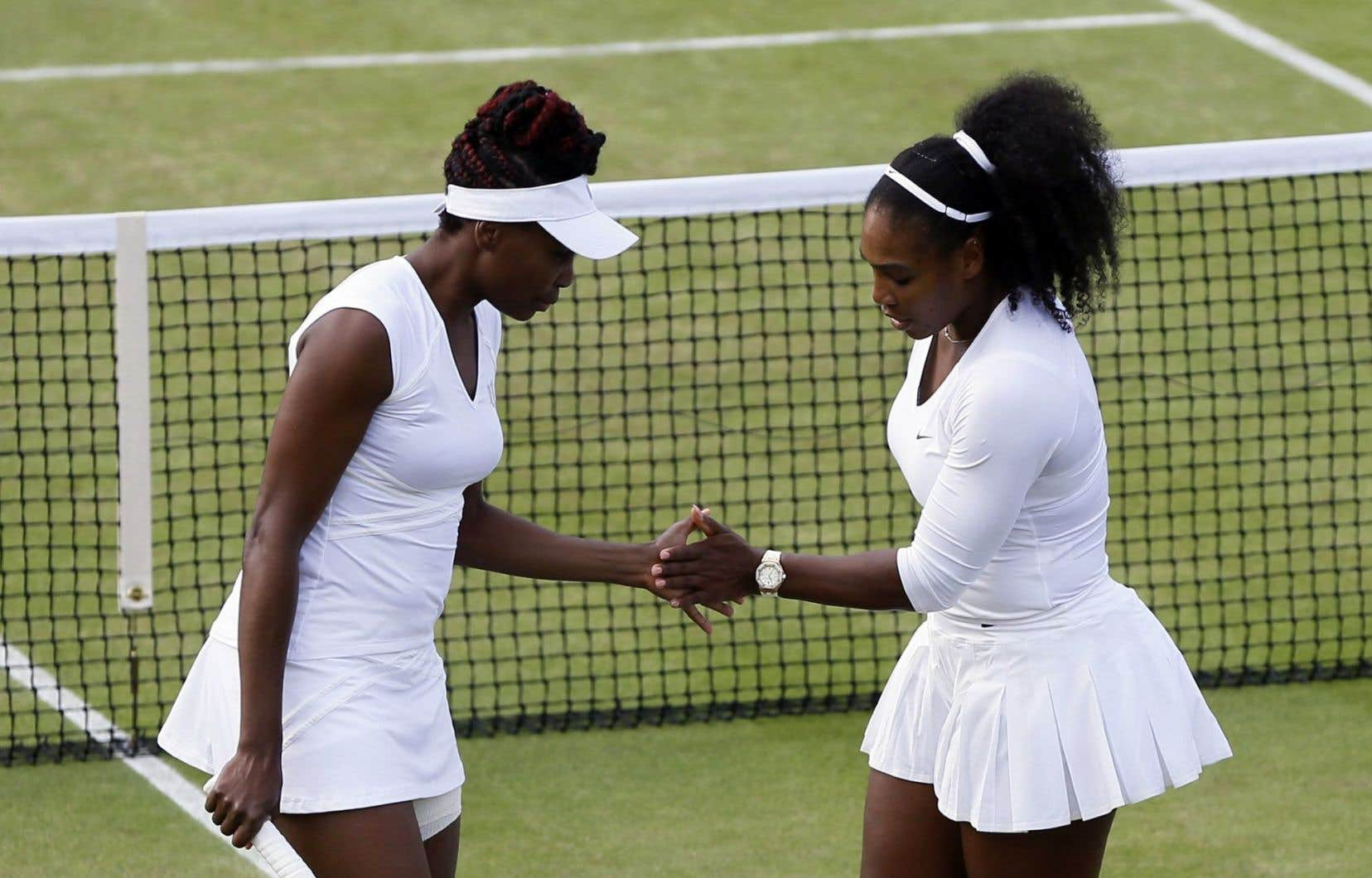 Les soeurs Venus et Serena Williams célèbrent un point marqué lors d'un match en double contreLucie Hradecka et Andrea Hlavackova, mardi.