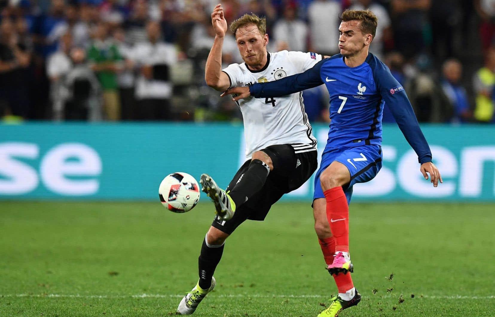 Le défenseur allemand Benedikt Hoewedes au coude à coude avec l'attaquant français Antoine Griezmann lors de la demi-finale, jeudi, à Marseille.