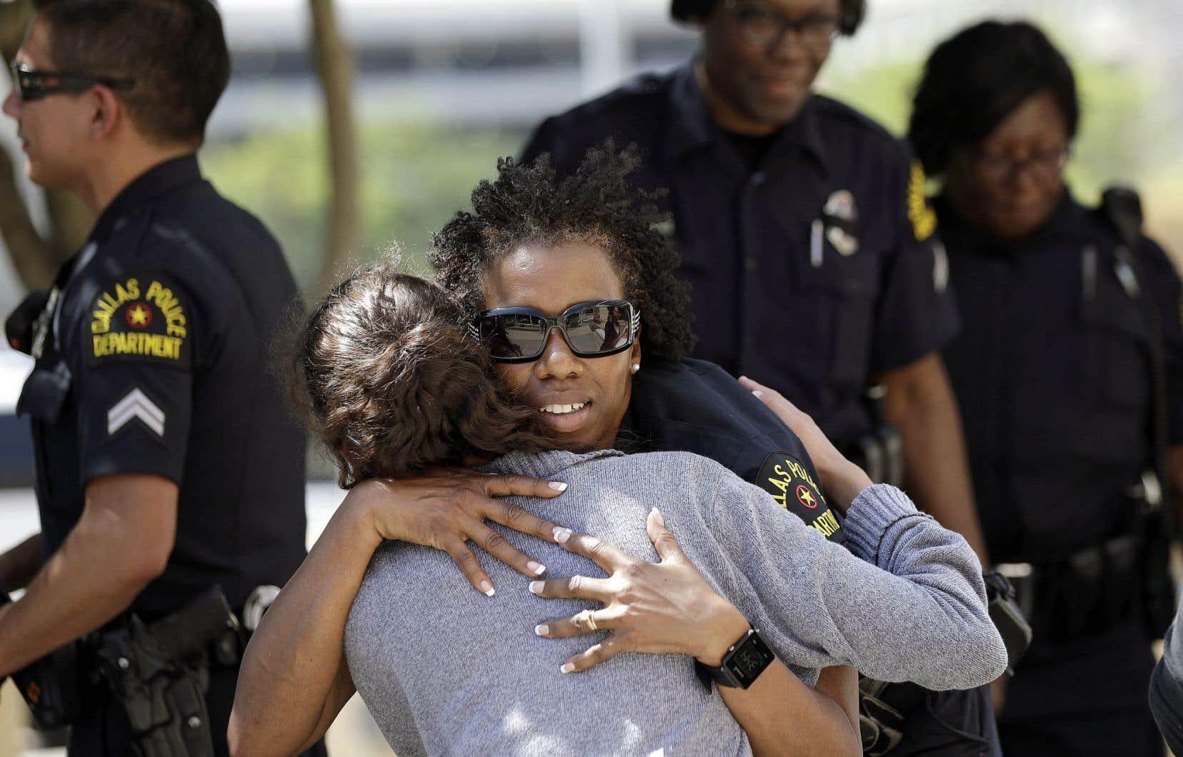Une citoyenne enlace une policière de Dallas après le choc encaissé par le corps policier, jeudi.