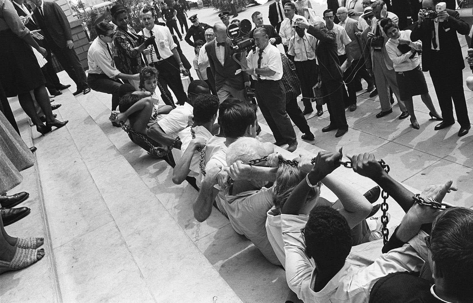 Noirs et Blancs se sont enchaînés devant l'hôtel de ville de New York, le 23août 1963, pour manifester contre la ségrégation encore pratiquée dans certains États américains. De telles manifestations pour les droits civils ont eu lieu dans plusieurs grandes villes des États-Unis, avec pour finale la marche à Washington.