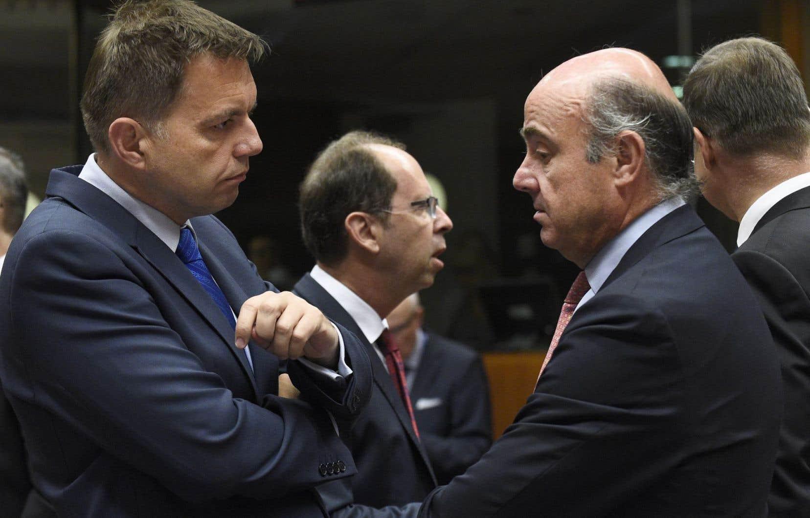 Le ministre espagnol des Finances, Luis de Guingos (à droite), discute avec son homologue slovaque, Peter Kazimir, à la réunion des ministres des Finances de la zone euro, mardi, à Bruxelles.