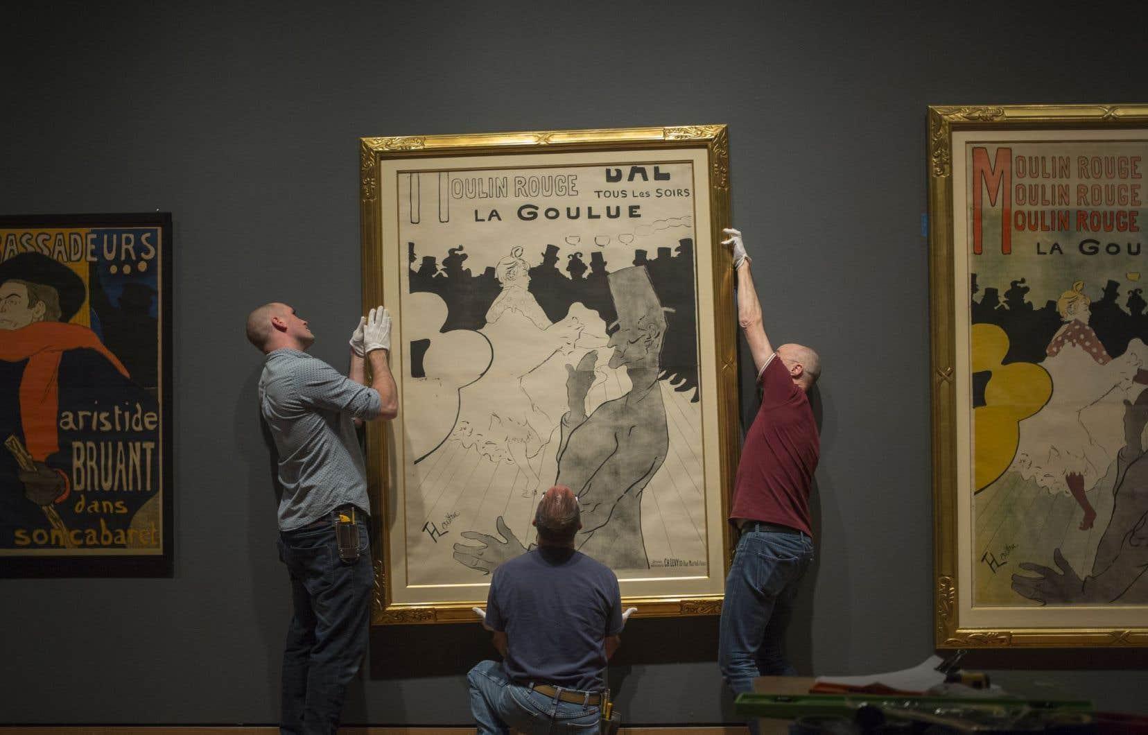 Trois hommes avec des gants blancs s'affairent à accrocher à un mur du Musée des beaux-arts de Montréal un immense tableau de Toulouse-Lautrec.