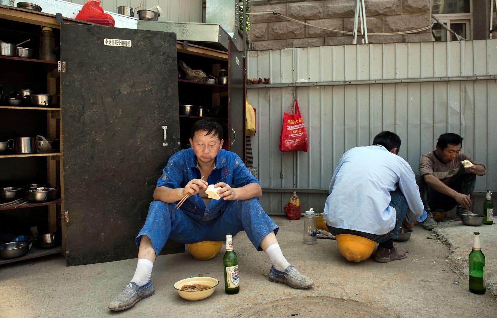 À Pékin, des ouvriers de la construction prennent leur repas de mi-journée avant de reprendre le travail.