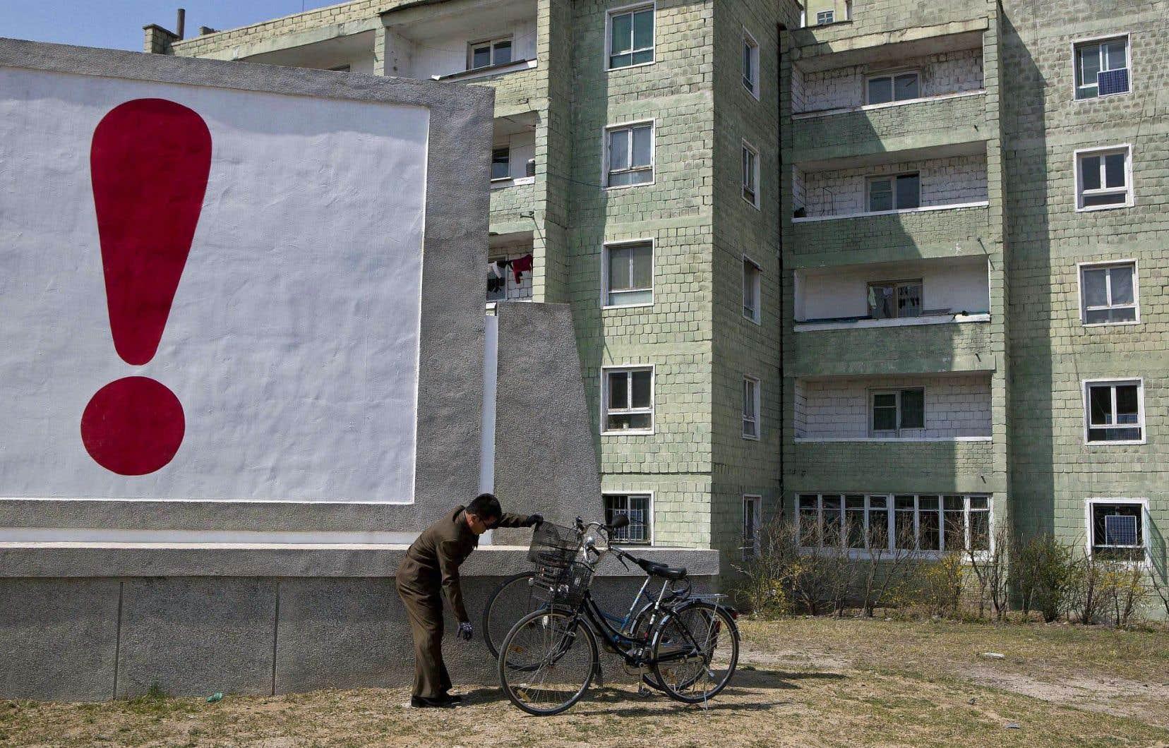 En Corée du Nord, la propagande gouvernementale est souvent exclamative. Ci-dessus, un homme vérifie son vélo devant un panneau qui affiche un slogan.