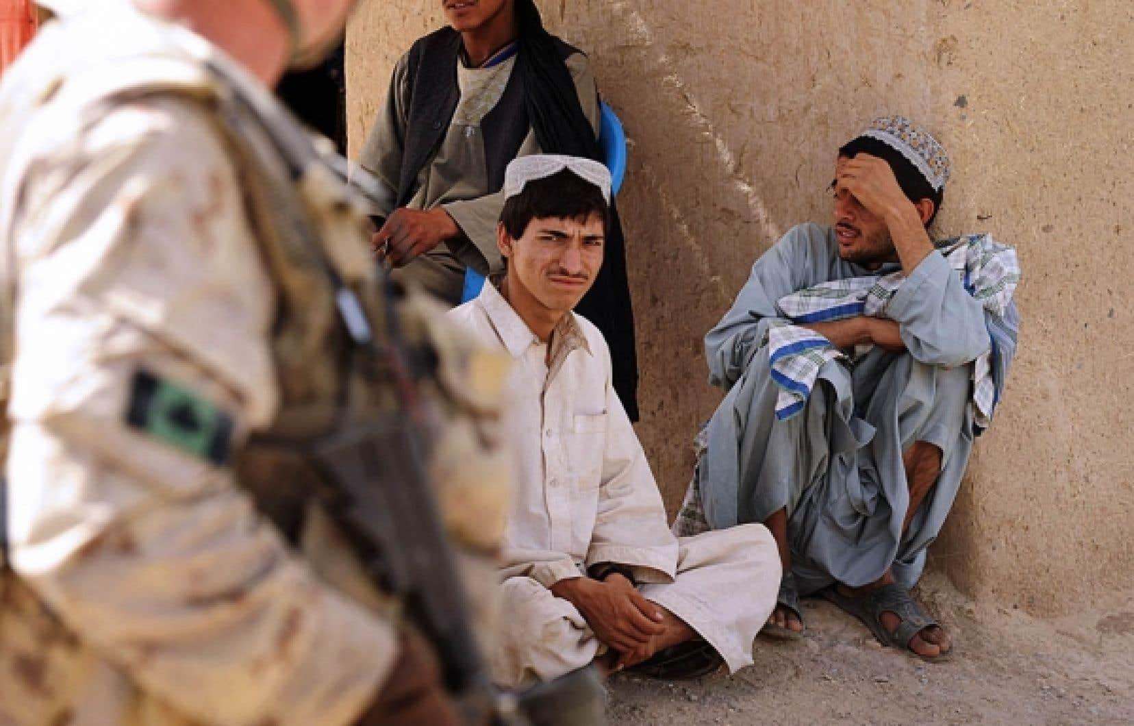 Des citoyens de la région de Kandahar observent un soldat canadien en train d'effectuer une patrouille.