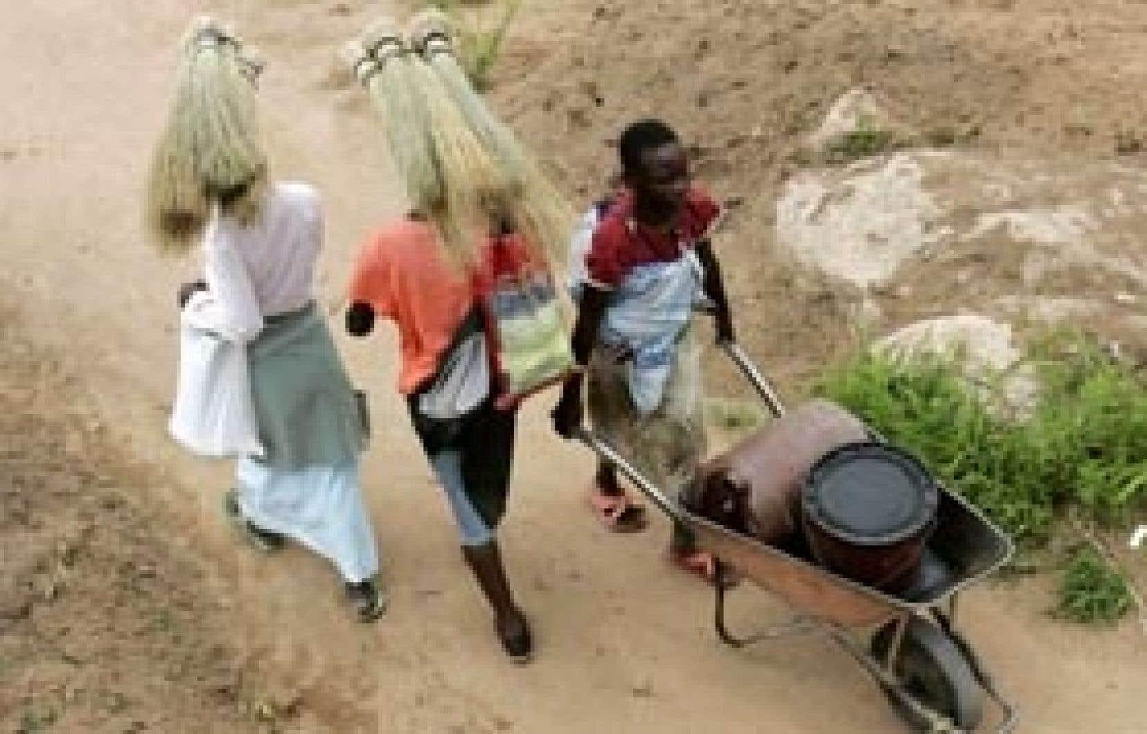 Pendant que Mugabe discute, des piétons s'affairent à tenter de contrer les conditions de vie inouïes du pays.