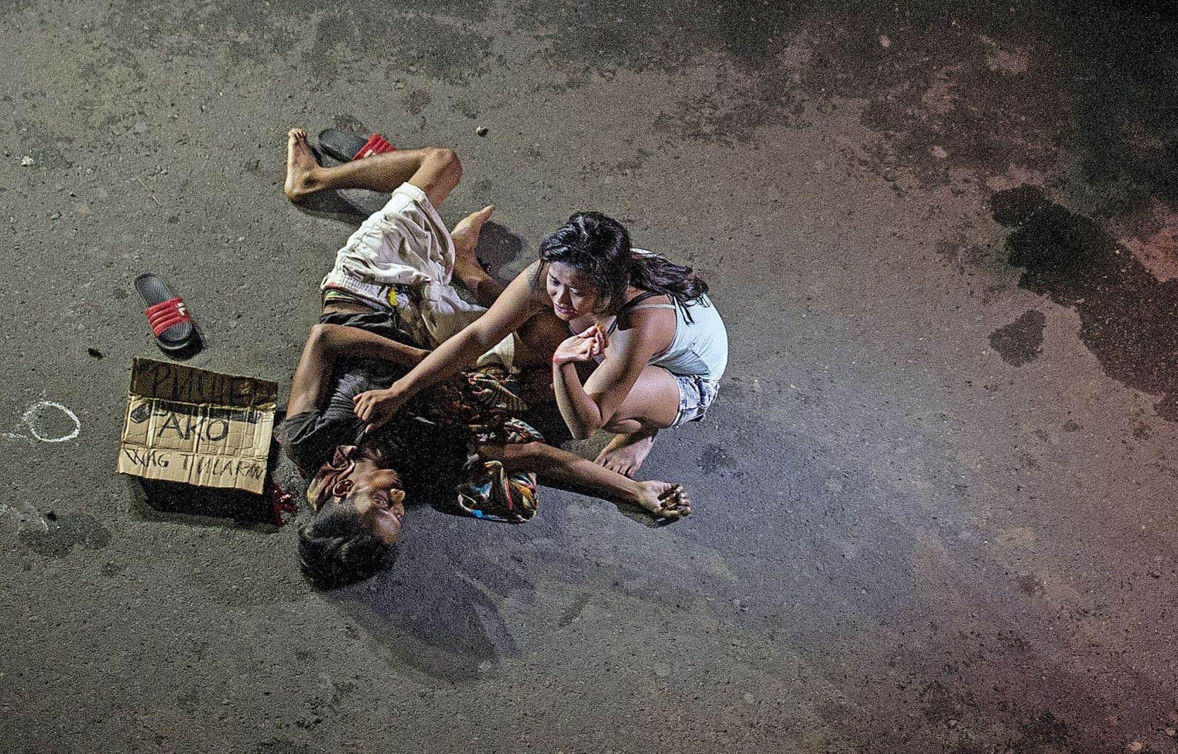 Jennilyn Olayres enlace son petit ami Michael Siaron, exécuté par un inconnu dans un quartier chaud de Manille, le 23 juillet dernier. À ses côtés, un carton clame: «Je suis un trafiquant».