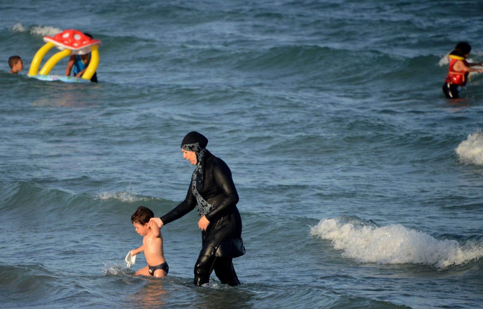 La ministre Vallée ne croit pas que le burkini, contraction de burqa et de bikini, soit très fréquent au Québec. Ci-dessus, une femme et son enfant sur une plage de Tunisie.