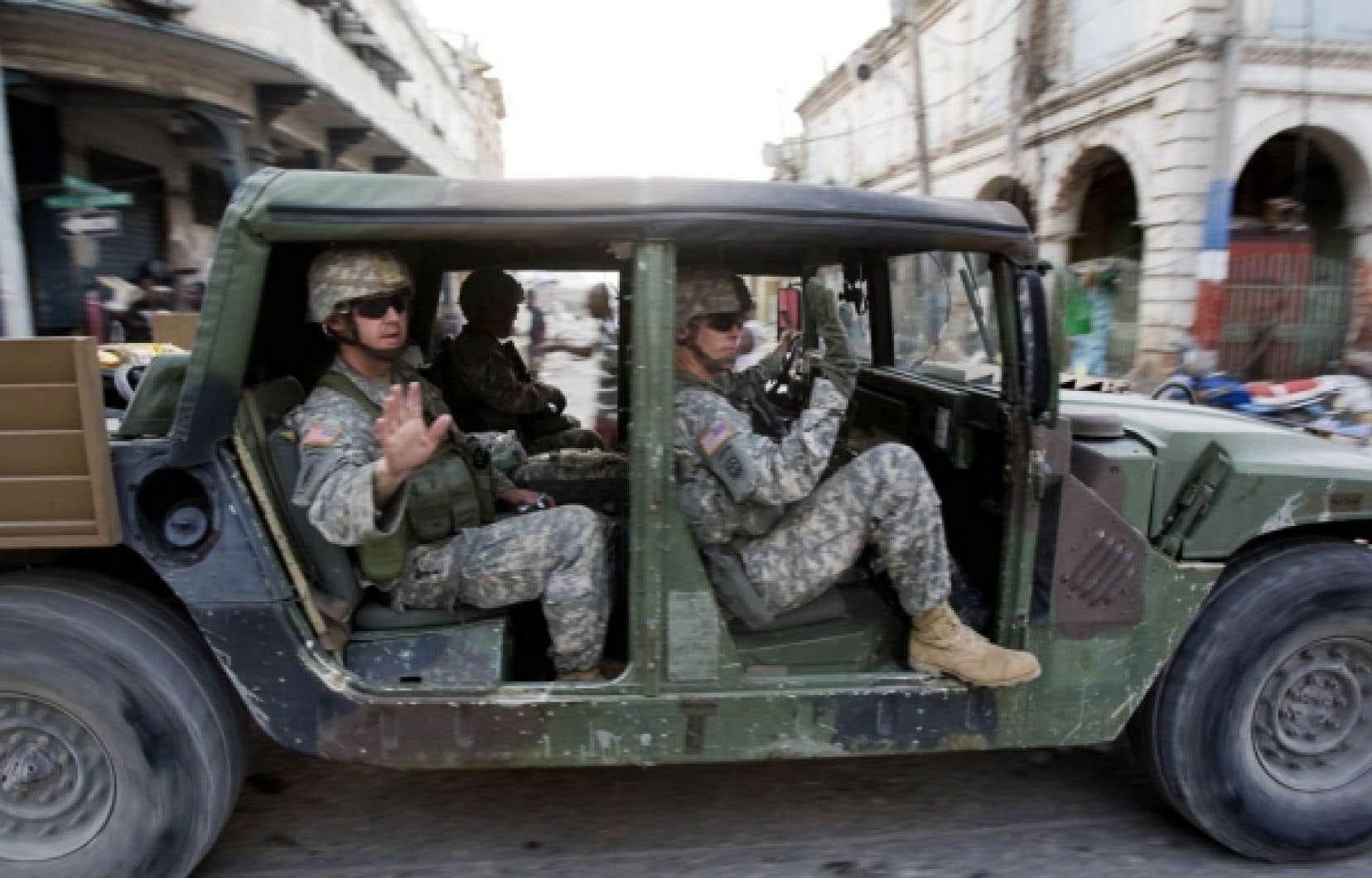 Des militaires américains saluaient les sinistrés du violent séisme du 12 janvier, hier, à Port-au-Prince. Le Pentagone a annoncé le déploiement de 4000 soldats supplémentaires en Haïti, alors que plusieurs voix s'élèvent pour désapprouver sa mainmise sur les opérations de secours.