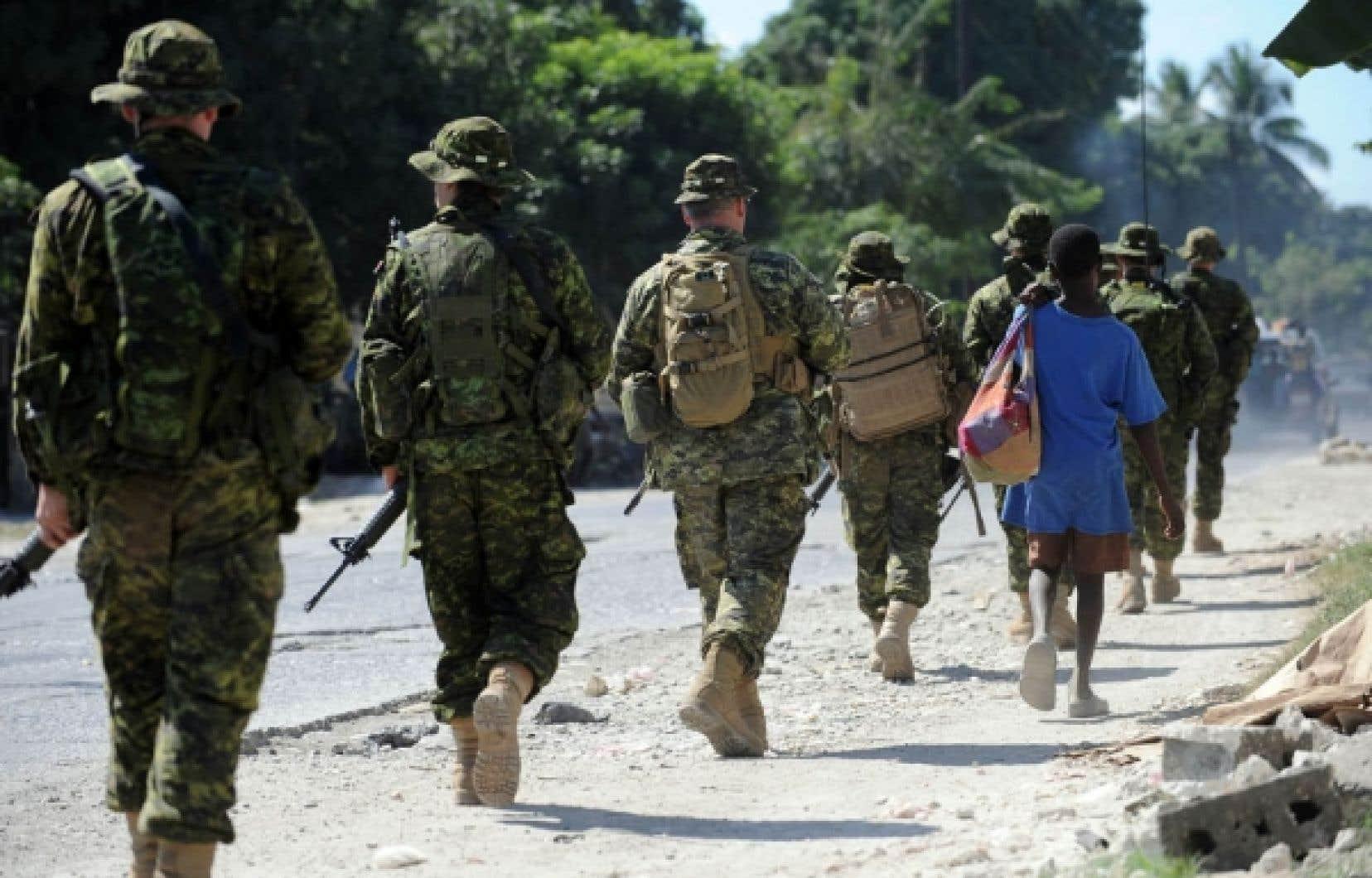 Des militaires canadiens patrouillent dans une rue de Léogâne. Les Canadiens sont fiers de voir leurs soldats partir pour Haïti où ils aideront un peuple de sinistrés à se relever. Mais ce déploiement s'ajoute à d'autres missions qui risquent de compromettre la qualité d'une éventuelle intervention au pays, en cas de catastrophe.