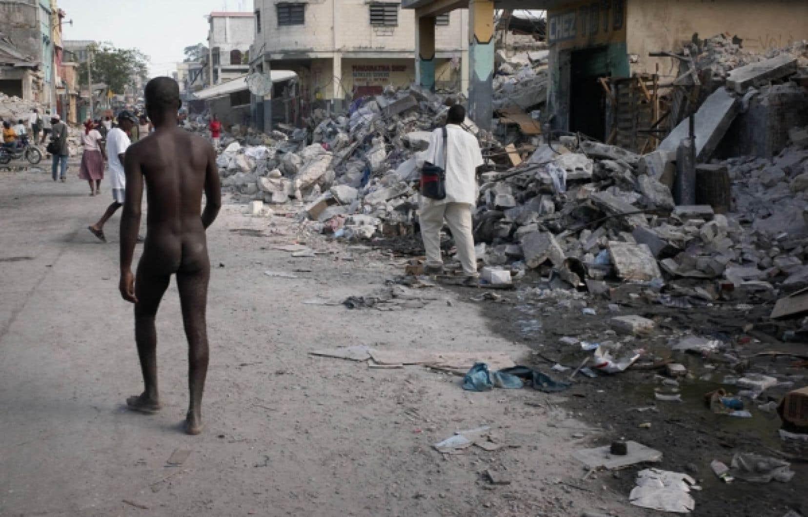 Dépossédé de tout, un homme — nu — marche dans une rue de Port-au-Prince.