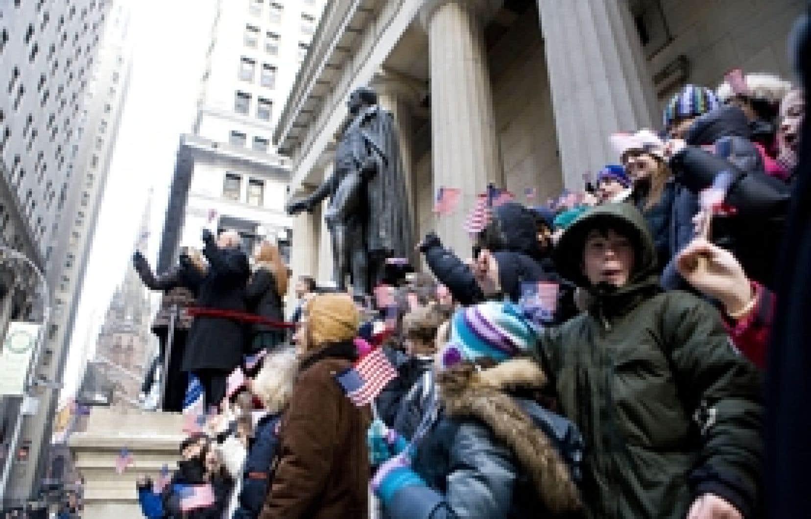 Des écoliers agitent des drapeaux américains pendant que des dignitaires du NYSE sonnent la cloche marquant l'ouverture des échanges à la Bourse de New York. Pour souligner l'investiture du président Barack Obama, la cérémonie quotidienne a ex