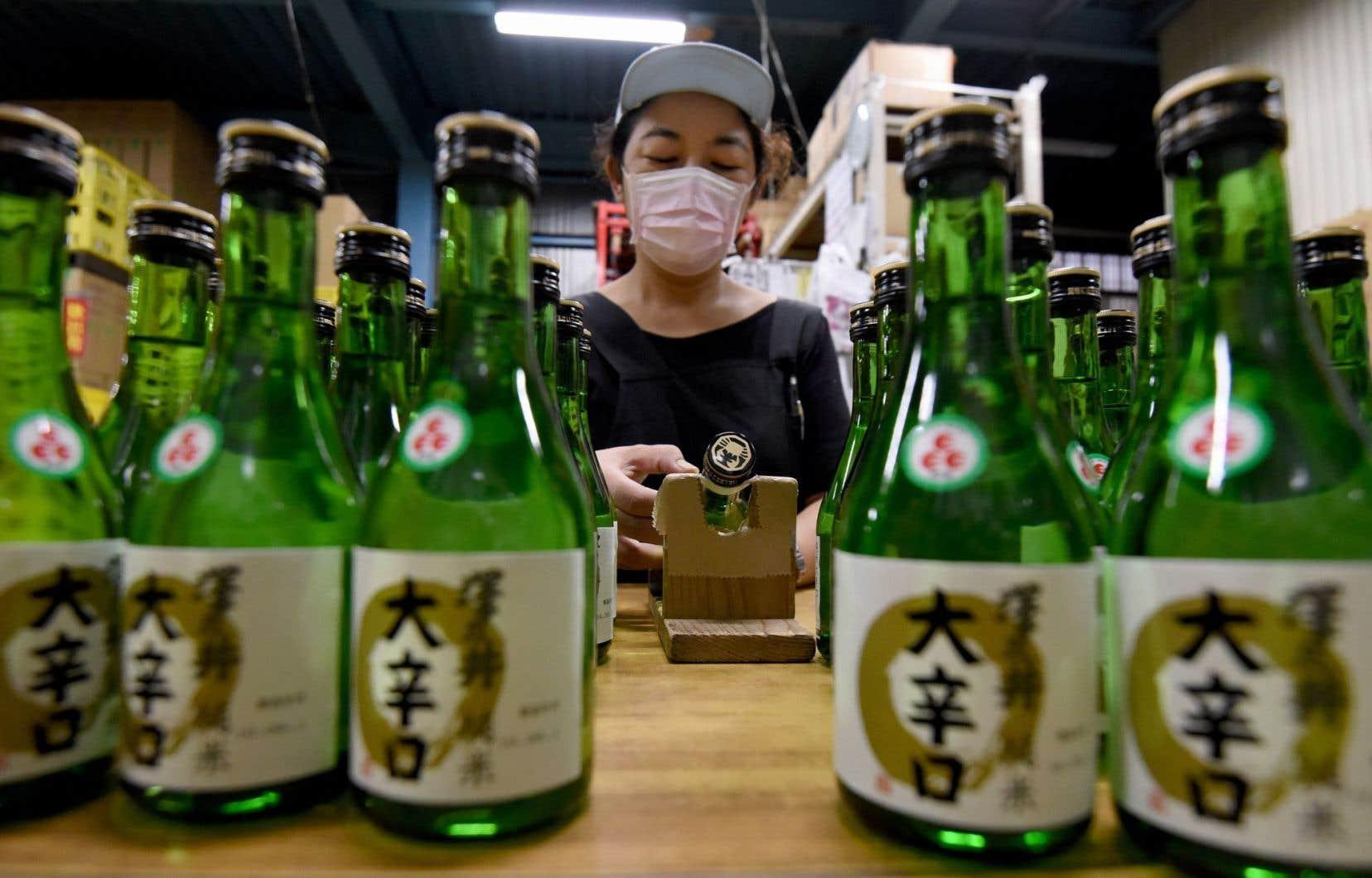 Une employée de la brasserie Ozawa Shuzo applique des étiquettes sur des bouteilles de saké.
