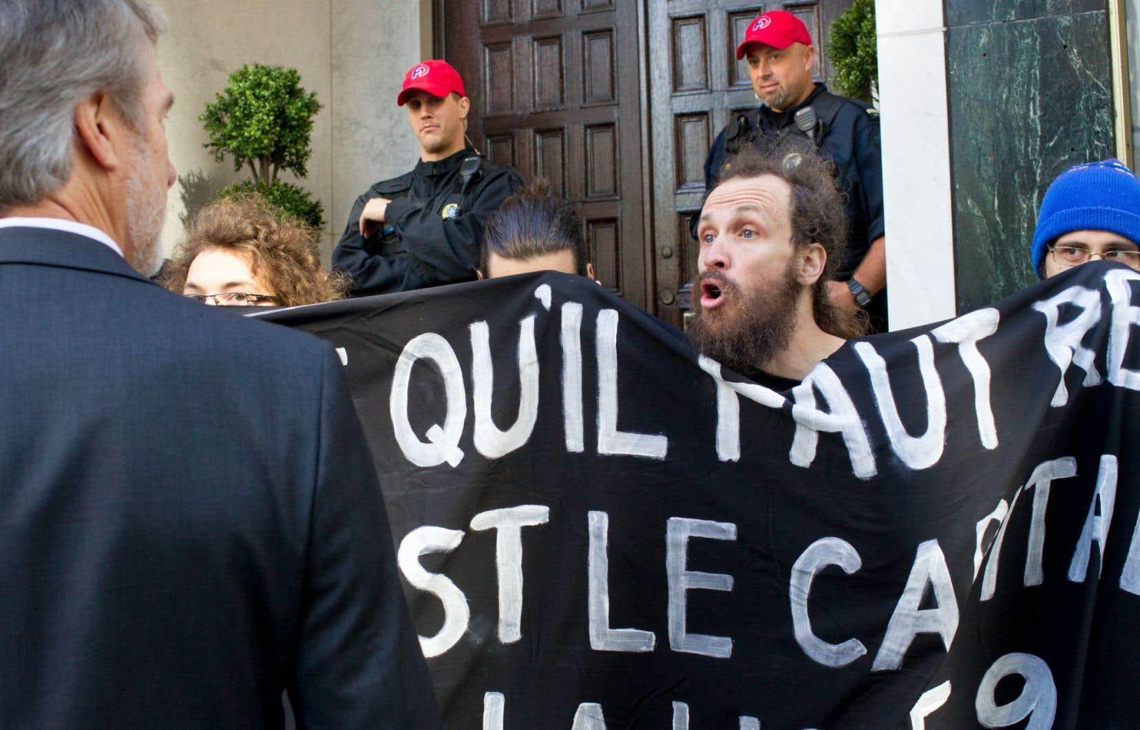 Des opposants au projet de pipeline Énergie Est ont manifesté jeudi devant le club privé St-James, au centre-ville de Montréal, sous la surveillance des services policiers.