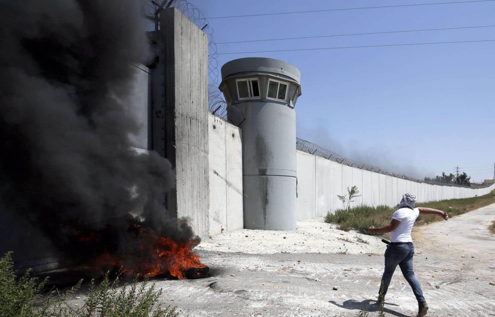 Un jeune Palestinien lance des pierres en direction d'un check point près de Qalandiya, là où une jeune femme a été abattue par des gardes privés en avril dernier parce qu'ils la soupçonnaient de vouloir les attaquer.