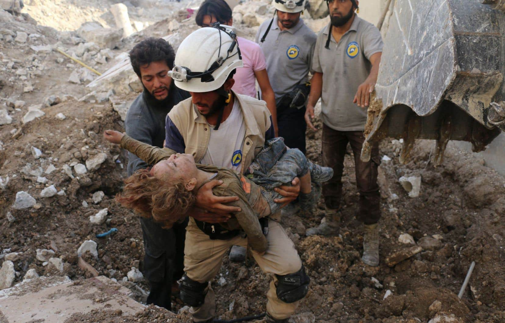 Un travailleur humanitaire porte le corps d'un jeune enfant après qu'il eut été dégagé des décombres causés par un raid aérien gouvernemental dans le quartier rebel de Karm Homad, à Alep.