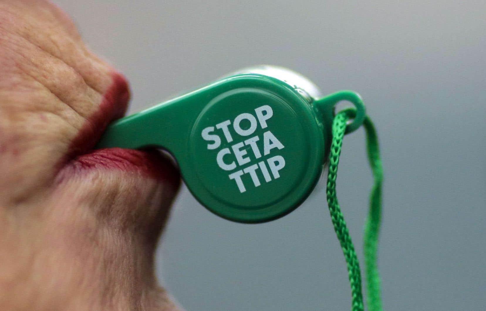 À Berlin, une opposante à l'accord de libre-échange entre l'Union européenne et le Canada manifestait mercredi devant la chancellerie. CETA est l'acronyme anglais pour l'accord Canada–UE tandis que TTIP réfère au projet de libre-échange UE–É.-U.