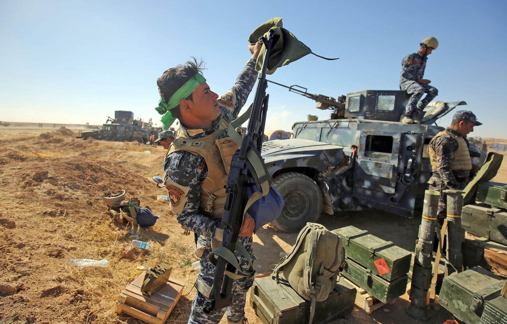 Un membre des forces policières irakiennes se préparait dimanche à l'opération pour la reprise de Mossoul à la base militaire de Qayyarah, située à 60 kilomètres de là.