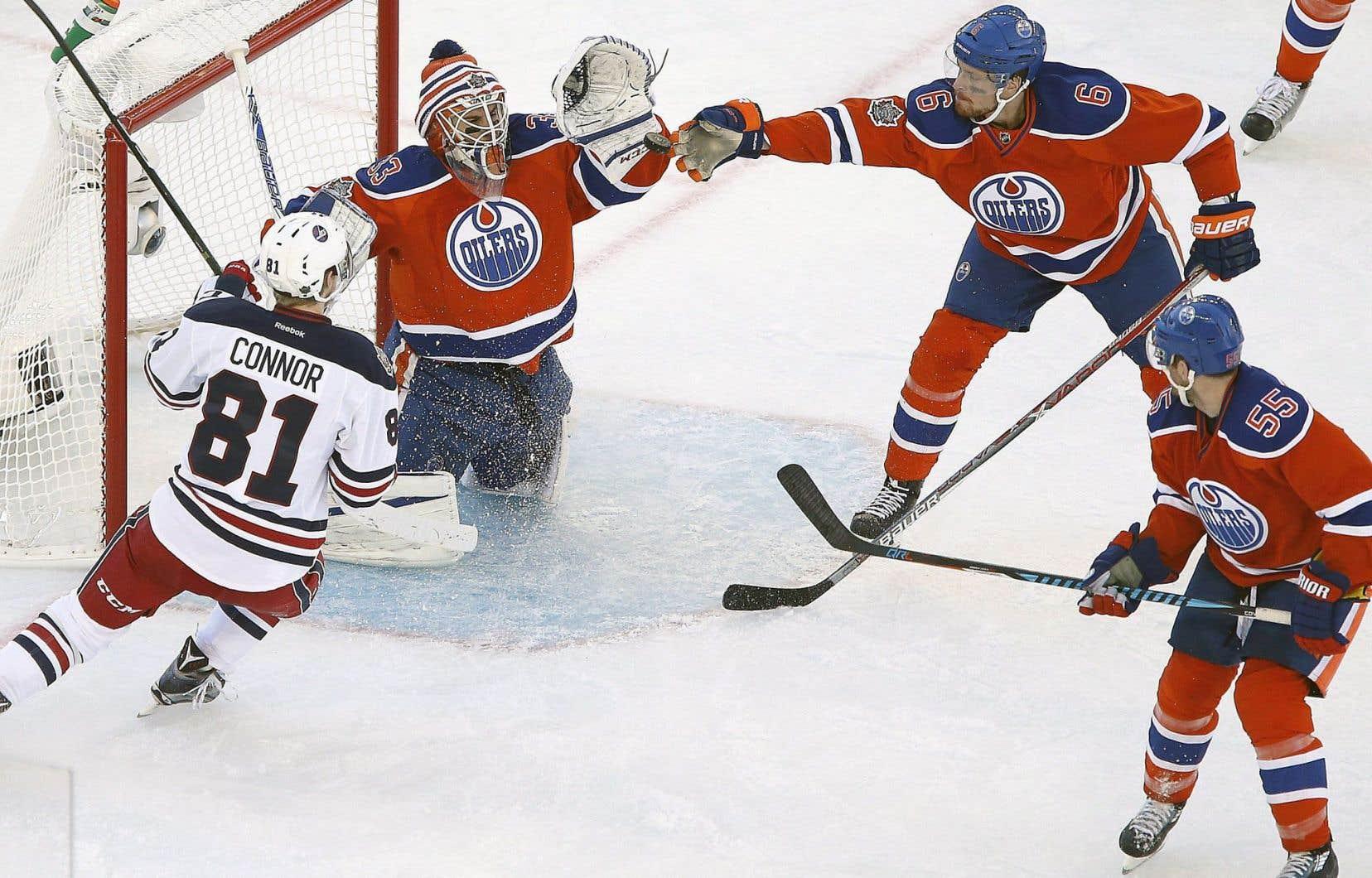 Adam Larsson, des Oilers, essaie d'arrêter la rondelle devant la cage du gardien de l'équipe, Cam Talbot, qui a effectué 31 arrêts au cours de la rencontre en plein air.