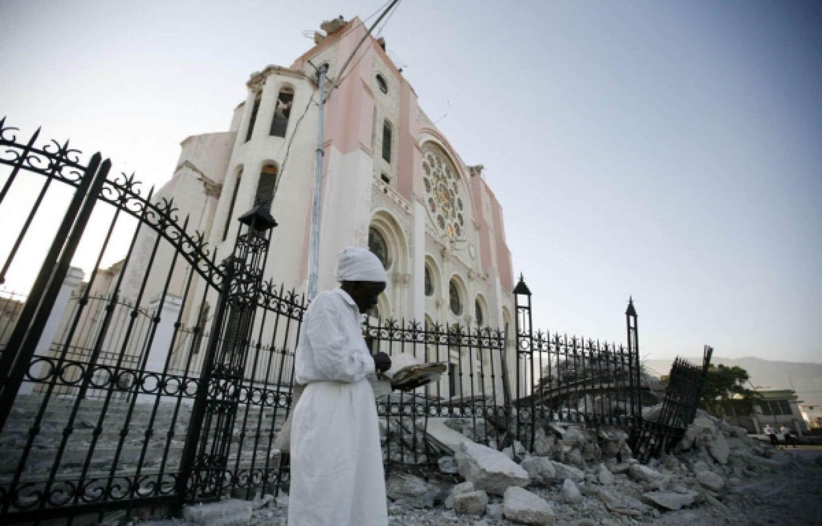 Une femme prie devant les ruines de la cathédrale de Port-au-Prince.