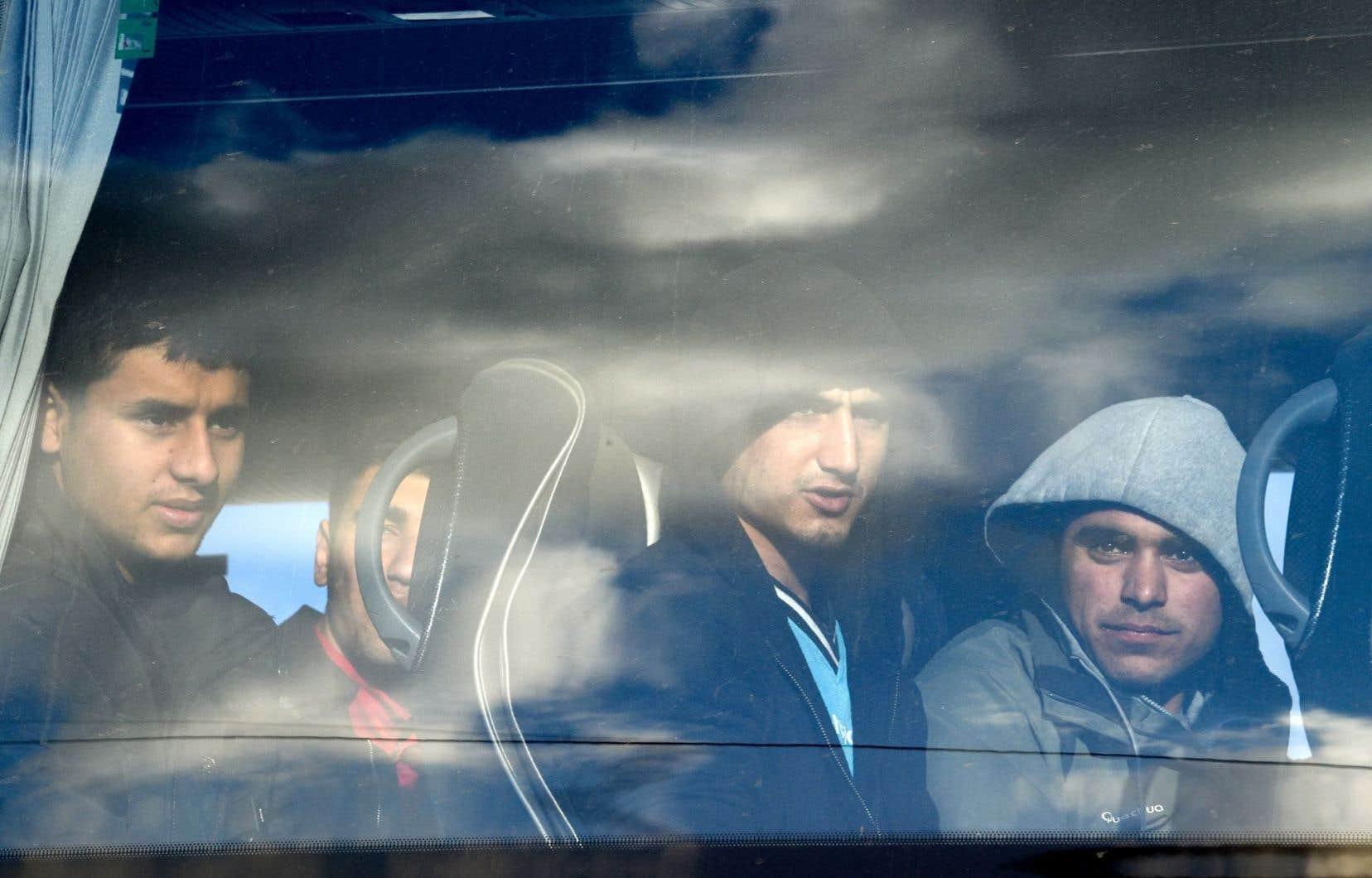 Des migrants photographiés à travers la vitre d'un autobus qui les conduit du camp de Calais jusqu'à une autre commune en France.