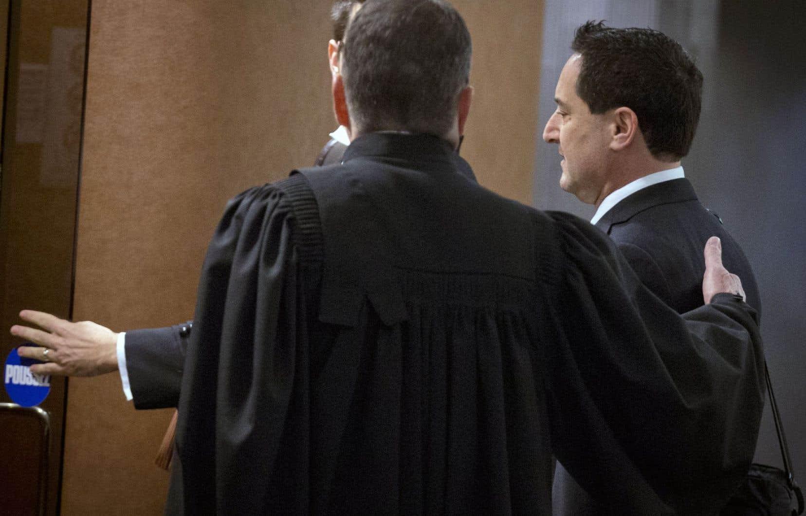 Michael Applebaum entre dans la salle du palais de justice de Montréal en compagnie de son avocat.