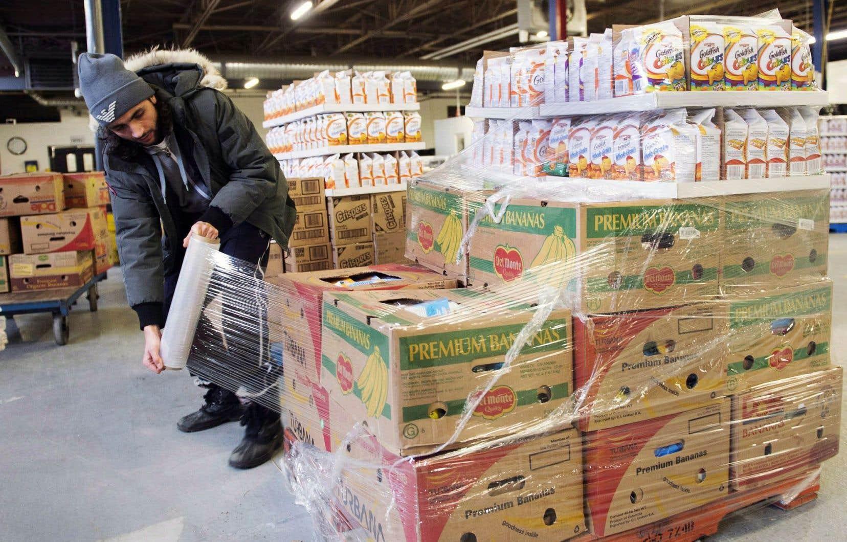 Un employé emballe des denrées au centre de distribution de Moisson Montréal.