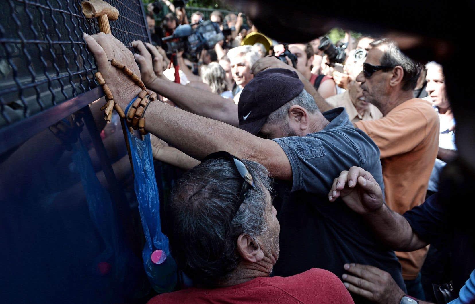 Des retraités grecs tentent de repousser un bus de police qui entrave le chemin vers le bureau du premier ministre, Alexis Tsipras , durant une manifestation contre les coupes des montants de retraite, en octobre dernier, à Athènes.